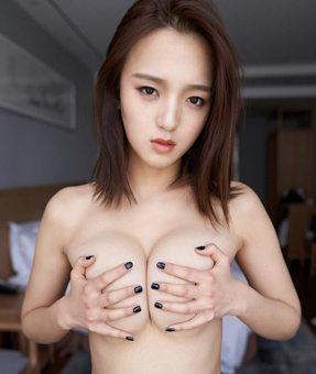 Fair skinned Busty Korean escort holding her breasts